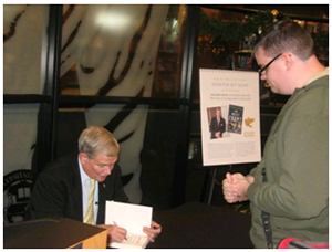U.S. Sen. Kit Bond signs a copy of his new book