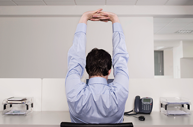 Man sitting at workstation, stretching with fingers interlaced