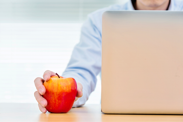 Man at laptop holding red apple